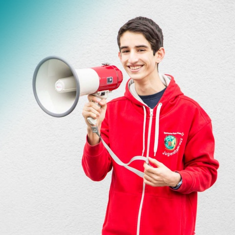 Ein Jugendrotkreuzler hält ein Megaphone in der Hand